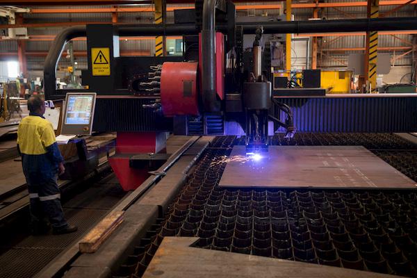 Man operating a steel cutter machine